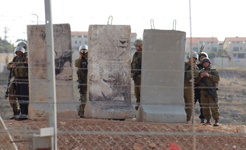 Israeli soldiers guarding a settlement built on the land of the West Bank village of Nilin (Ahmad Mesleh/Stop the Wall)