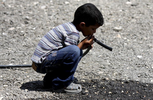 A Palestinian Bedouin child drinks water from a pipe near his tent on the road between Jericho and Ramallah