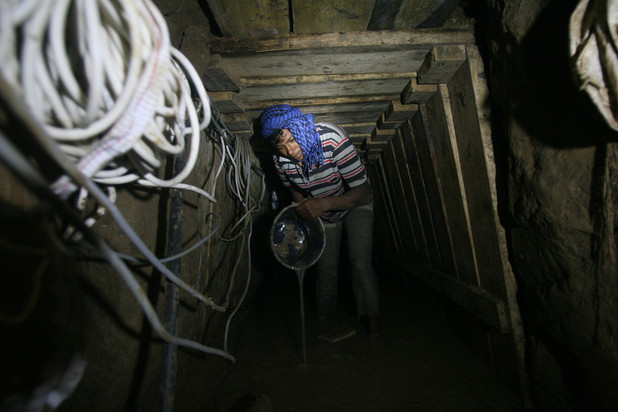 A Palestinian tunnel worker uses a bucket to empty water from a smuggling tunnel dug beneath the Gaza-Egypt border in Rafah